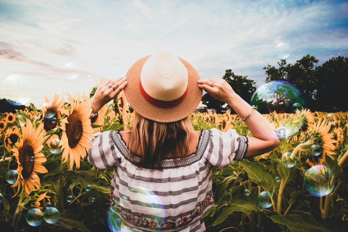 Frau mit Hut in Sonnenblumenfeld