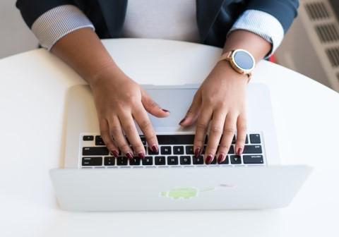 Hände, die an einem Laptop schreiben