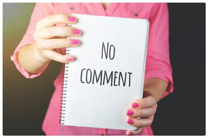 """Eine Frau hält ein """"Kein Kommentar""""-Schild"""