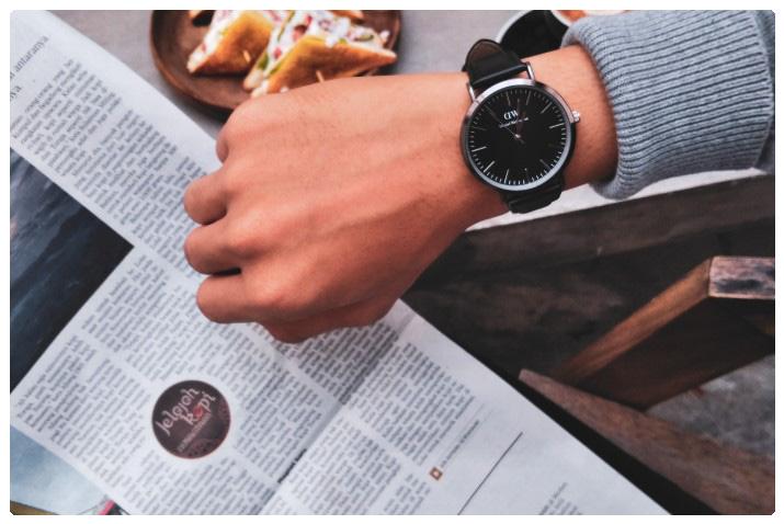 Mann schaut beim Zeitung lesen auf die Uhr
